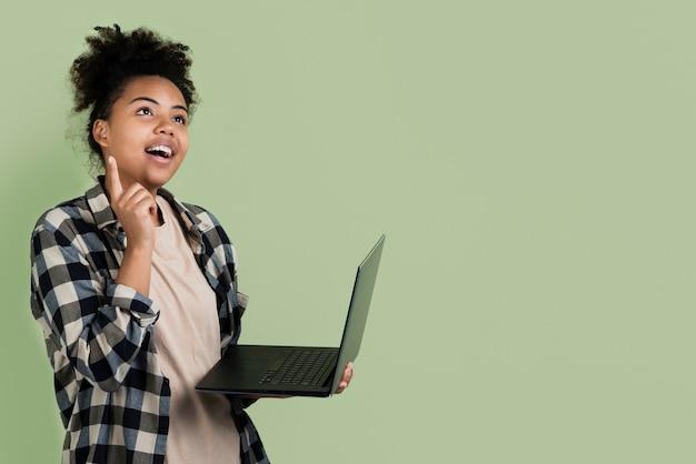 Denkende frau beim halten des laptops