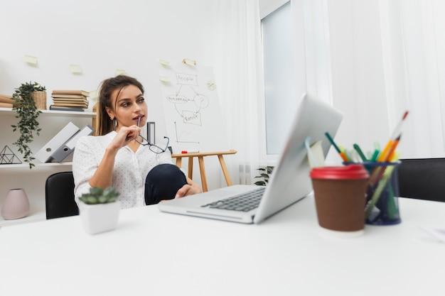 Denkende frau, die in ihrem büro sitzt