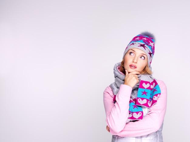 Denkende frau in winterkleidung, die aufschaut
