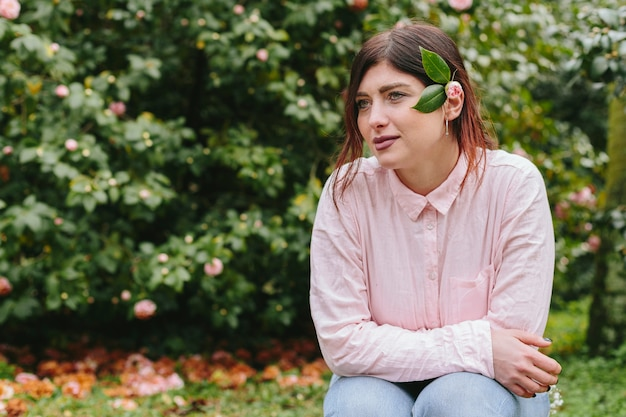 Denkende frau mit anlage im haar nahe den rosa blumen, die auf grünen zweigen wachsen