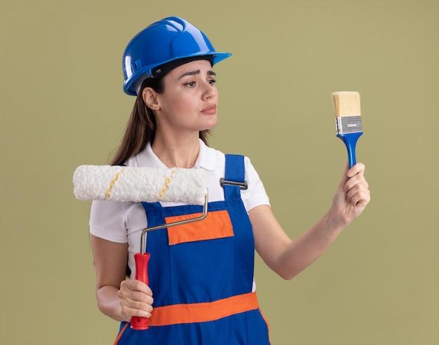 Denkende junge baumeisterfrau in uniform, die rollpinsel hält und pinsel in ihrer hand lokalisiert auf olivgrüner wand betrachtet