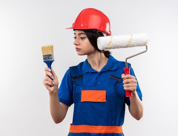 Denkende junge baumeisterin in uniform hält und betrachtet walzenbürste mit pinsel isoliert auf weißer wand