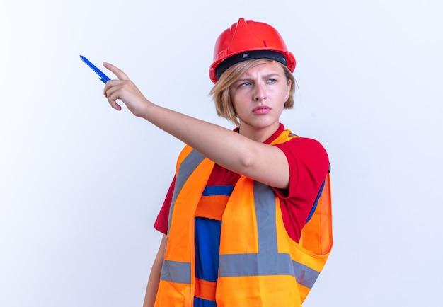 Denkende junge baumeisterin in uniform zeigt seitlich mit bleistift auf weißem hintergrund