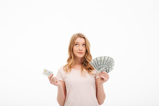 Denkende junge dame, die geld und kreditkarte hält.