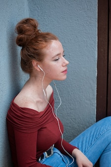 Denkende junge frau, die musik hört