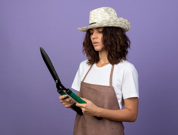 Denkende junge gärtnerin in uniform, die gartenhut hält und schermaschinen betrachtet