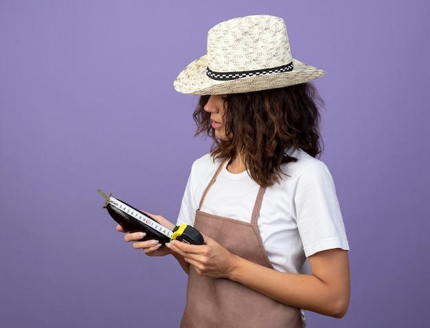 Denkende junge gärtnerin in uniform mit gartenhut, die auberginen mit maßband misst