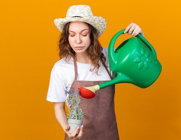 Denkende junge gärtnerin mit gartenhut, die blume im blumentopf mit gießkanne gießt