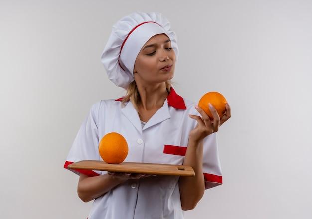 Denkende junge kochfrau, die kochuniform trägt, die orange auf schneidebrett in ihren händen schaut