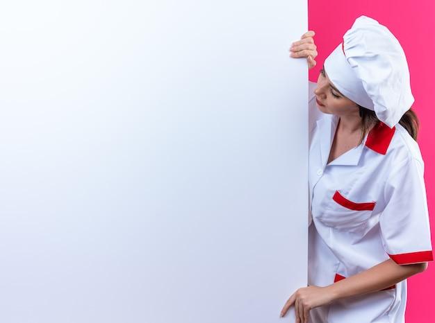 Denkende junge köchin, die kochuniform trägt, steht in der nähe der weißen wand isoliert auf rosa wand mit kopierraum