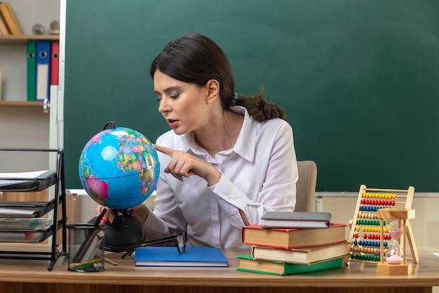 Denkende junge lehrerin, die am tisch mit schulwerkzeugen sitzt und den finger auf den globus im klassenzimmer hält