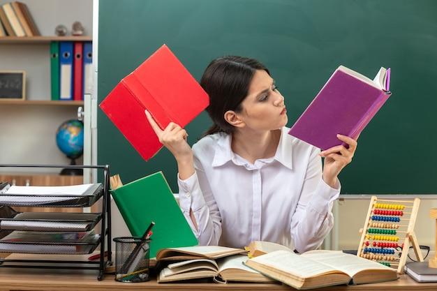 Denkende junge lehrerin, die ein buch hält und liest, das am tisch mit schulwerkzeugen im klassenzimmer sitzt