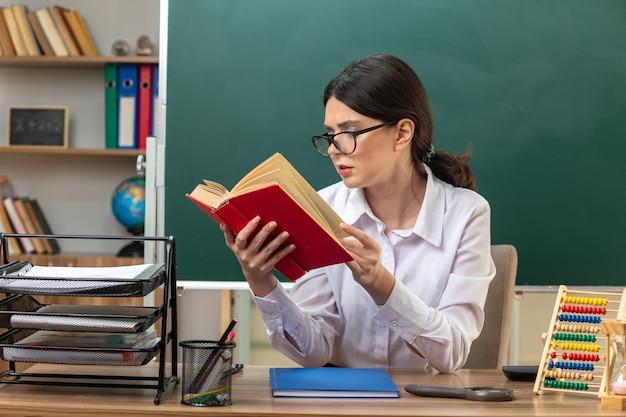 Denkende junge lehrerin, die eine brille trägt und ein buch liest, das am tisch mit schulwerkzeugen im klassenzimmer sitzt?