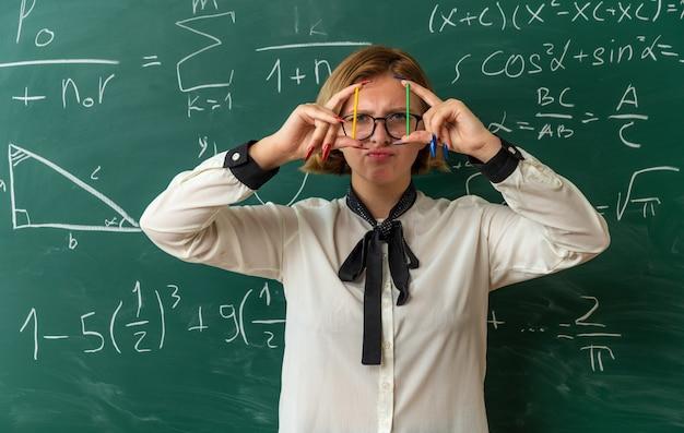 Denkende junge lehrerin mit brille, die vor der tafel steht und bleistifte im klassenzimmer hält