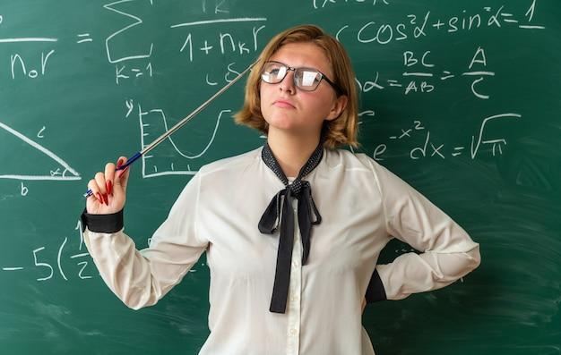 Denkende junge lehrerin mit brille, die vor der tafel steht und einen zeiger hält, der die hand auf die hüfte im klassenzimmer legt