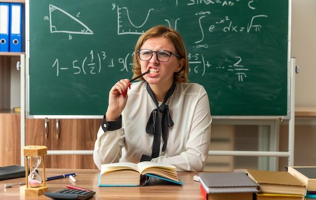 Denkende junge lehrerin mit brille sitzt am tisch mit schulmaterial, das bleistift im klassenzimmer hält