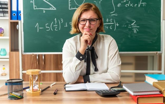 Denkende junge lehrerin mit brille sitzt am tisch mit schulmaterial, das im klassenzimmer am kinn gegriffen hat