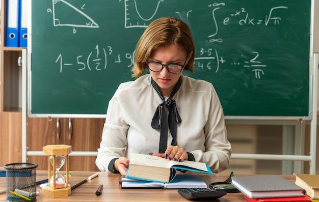 Denkende junge lehrerin mit brille sitzt am tisch mit schulwerkzeugen, die ein buch im klassenzimmer lesen