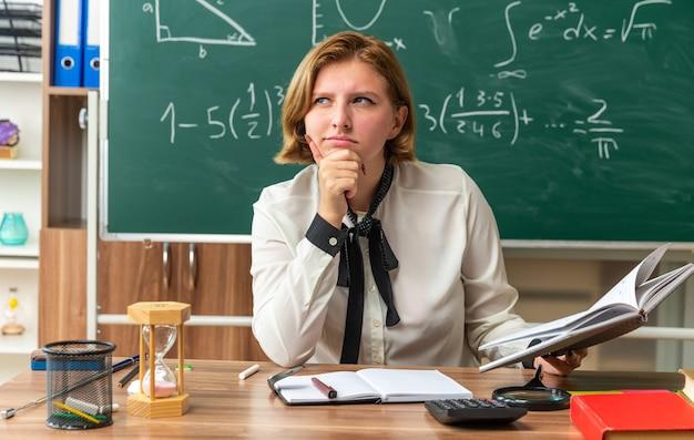 Denkende junge lehrerin sitzt am tisch mit schulmaterial, das ein buch hält, das kinn im klassenzimmer gepackt hat