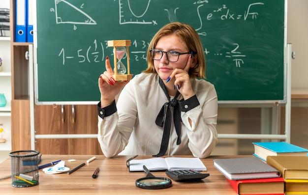Denkende junge lehrerin sitzt am tisch mit schulwerkzeugen, die im klassenzimmer eine sanduhr halten und betrachten