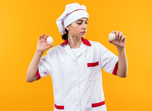 Denkende junge schöne frau in kochuniform, die eier auf orangefarbener wand isoliert hält und betrachtet