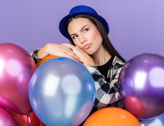 Denkende junge schöne frau mit partyhut, die hinter luftballons steht, isoliert auf blauer wand