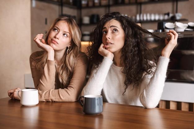 Denkende junge schöne freundinnen sitzen im café und schauen beiseite