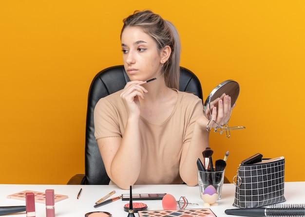 Denkende junge schöne mädchen sitzt am tisch mit make-up-tools, die make-up-pinsel mit spiegel auf orangem hintergrund halten