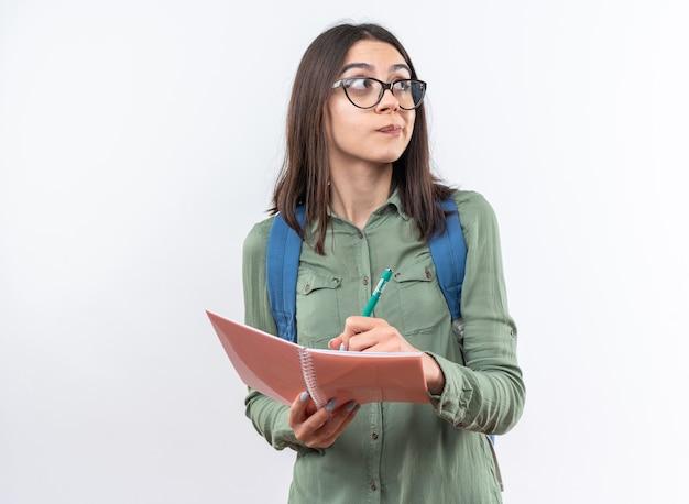 Denkende junge schulfrau mit brille mit rucksack, die etwas auf dem notebook schreibt