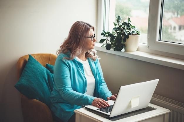 Denkende kaukasische ältere frau mit blonden haaren und brillen, die am computer nahe dem fenster während der quarantäne arbeiten