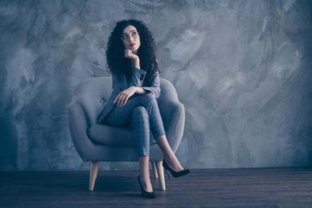 Denkende manager-mädchen sitzen im stuhl, der beine auf grauer wand kreuzt