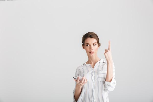 Denkende schöne frau, die mit dem finger nach oben zeigt und das handy isoliert auf weißem hintergrund benutzt
