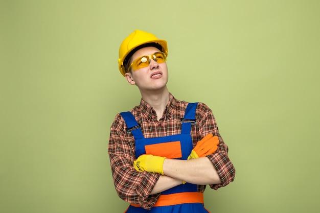 Denkende, seitlich kreuzende hände junger männlicher baumeister in uniform und handschuhen mit brille