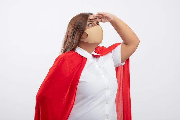 Denkende superheldenfrau mittleren alters, die medizinische maske trägt, die entfernung mit hand lokalisiert auf weiß betrachtet
