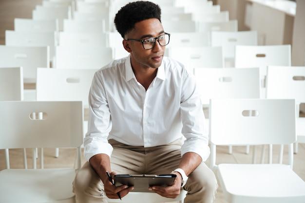 Denkender afrikanischer mann, der coworking mit zwischenablage sitzt