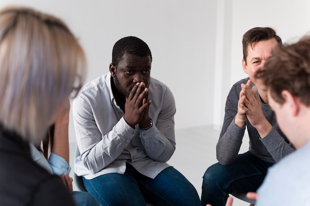 Denkender afroamerikanischer mann, der rehabilitationspatienten betrachtet