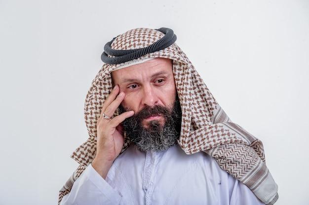 Denkender arabischer mann, der auf weißem hintergrund aufwirft.