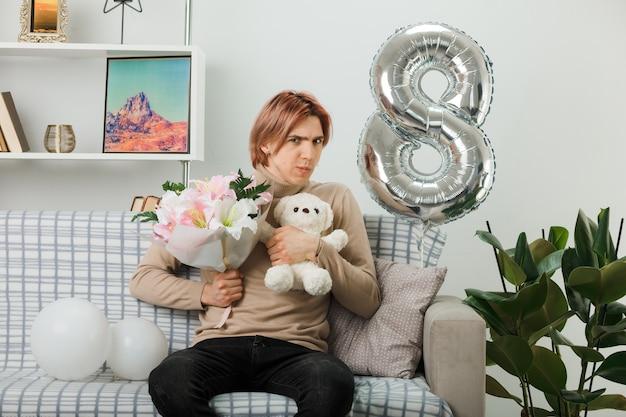 Denkender hübscher kerl am glücklichen frauentag, der blumenstrauß mit teddybär hält, der auf sofa im wohnzimmer sitzt