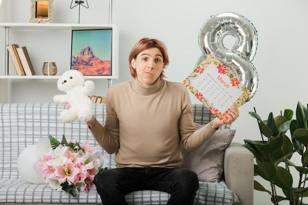 Denkender hübscher kerl am glücklichen frauentag, der teddybären mit kalender hält, der auf sofa im wohnzimmer sitzt