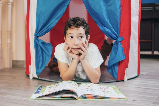 Denkender junge des tweens mit dem gelockten haar im spielzeugzelthaus, das zu hause buch liegt und liest