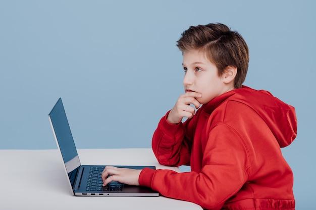 Denkender junge schaut zur seite in der nähe des laptops in rotem sweatshirt isolierte blaue hintergrundseitenansicht