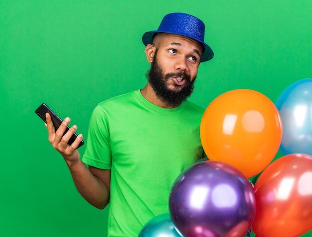 Denkender junger afroamerikaner mit partyhut, der luftballons mit telefon hält