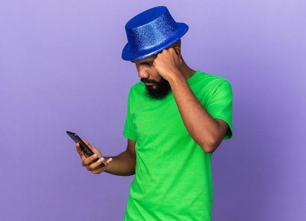 Denkender junger afroamerikanischer mann mit partyhut, der das telefon isoliert auf blauer wand hält und betrachtet