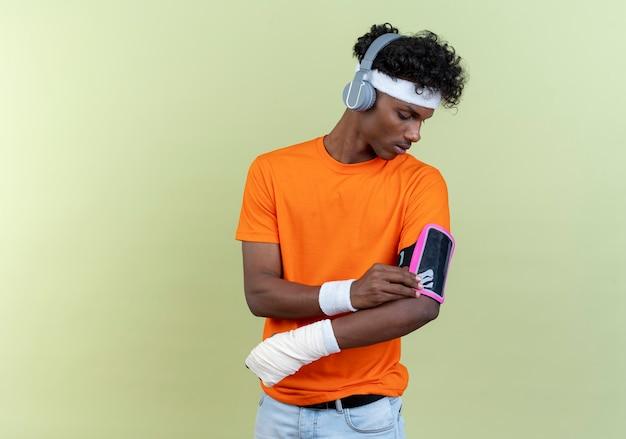 Denkender junger afroamerikanischer sportlicher mann mit stirnband und armband und telefonarmband in kopfhörern mit bondage-handgelenk