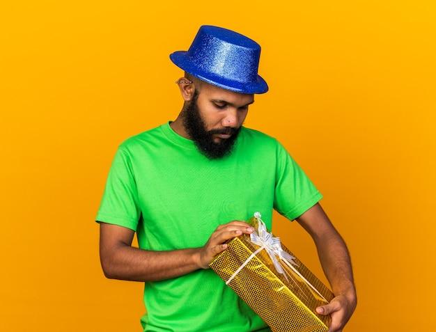 Denkender junger afroamerikanischer typ mit partyhut, der eine geschenkbox hält und betrachtet