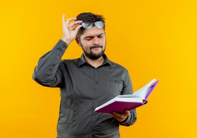 Denkender junger geschäftsmann, der brillen hält, die buch auf gelb halten und betrachten