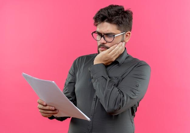 Denkender junger geschäftsmann, der brillen trägt, die papier halten und betrachten und hand auf wange lokalisiert auf rosa setzen