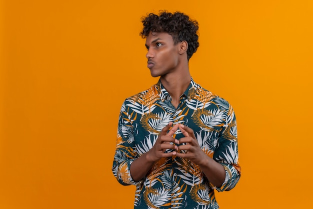 Denkender junger gutaussehender dunkelhäutiger mann mit lockigem haar im bedruckten hemd der blätter, das hände zusammen auf einem orangefarbenen hintergrund hält