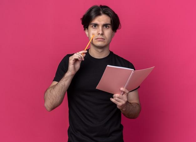 Denkender junger gutaussehender kerl, der ein schwarzes t-shirt trägt und ein notizbuch mit bleistift hält, isoliert auf rosa wand