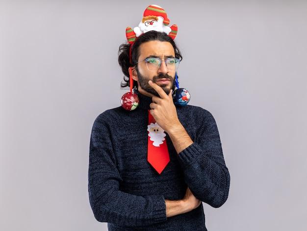 Denkender junger gutaussehender kerl, der weihnachtskrawatte mit haarbügel hängenden weihnachtsball auf ohren packte kinn lokalisiert auf weißem hintergrund